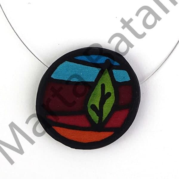Collar realizado en caucho y una aplicación de seda con un árbol.